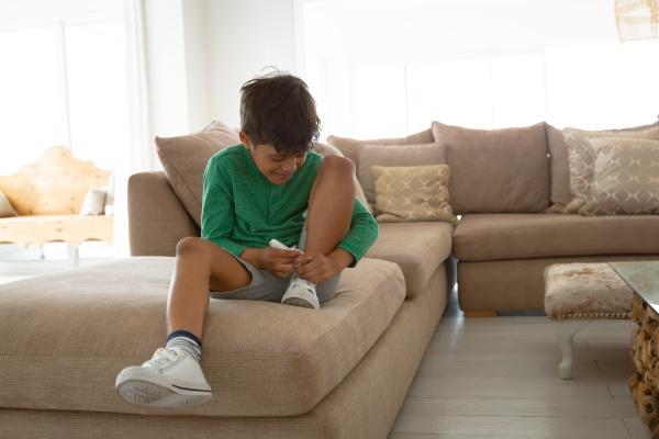 boy tying shoelace on sofa in