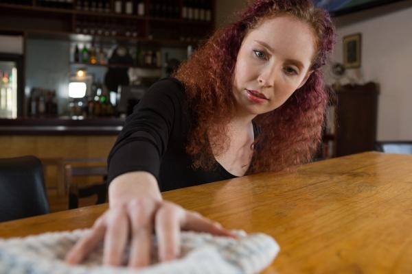 waitress cleaning bar counter