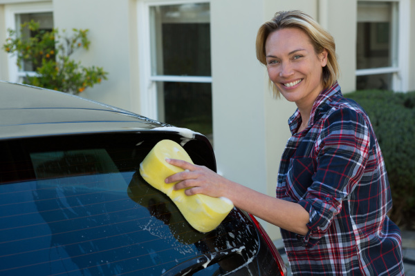 smiling woman cleaning her car with