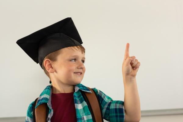 happy boy in graduation cap pointing