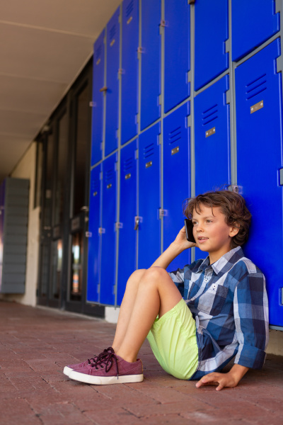 schoolboy talking on mobile phone while