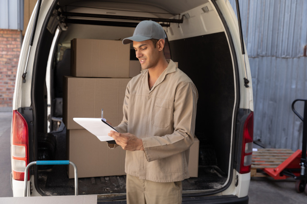 delivery man writing on clipboard near
