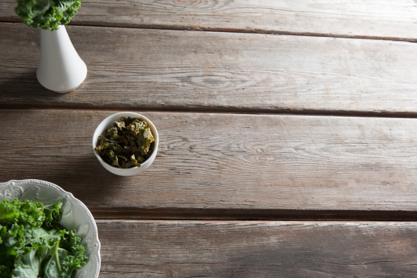 kale in containers on wooden table