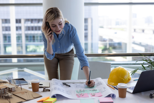blonde caucasian female architect talking on