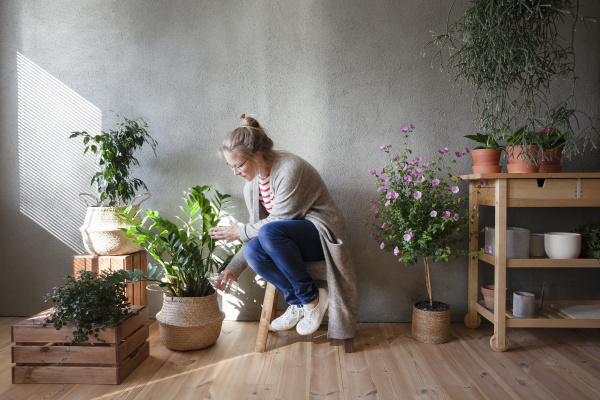 woman tending to potted plants in