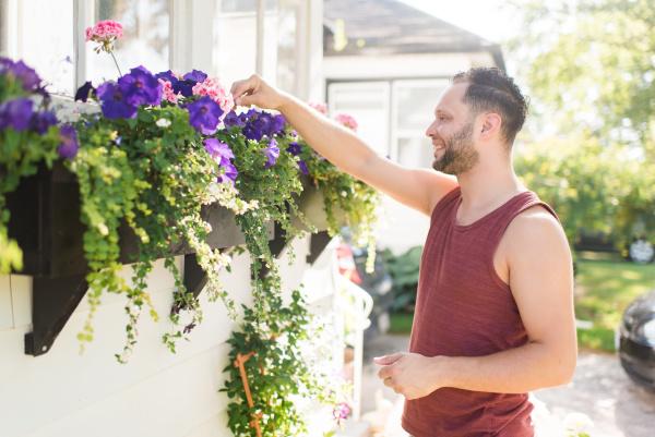 man tending to flowers in garden