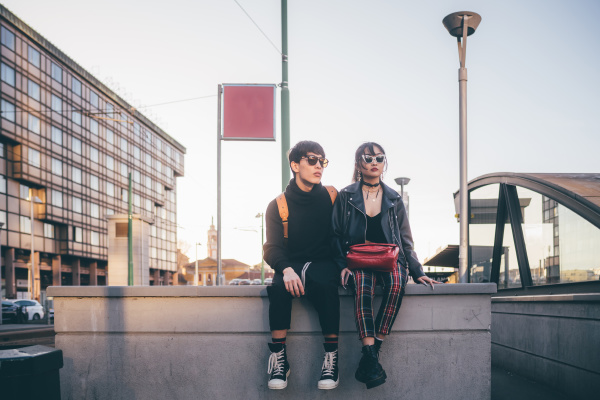 trendy couple waiting on concrete structure