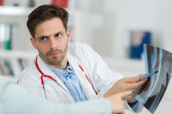 male doctor with patient looking at