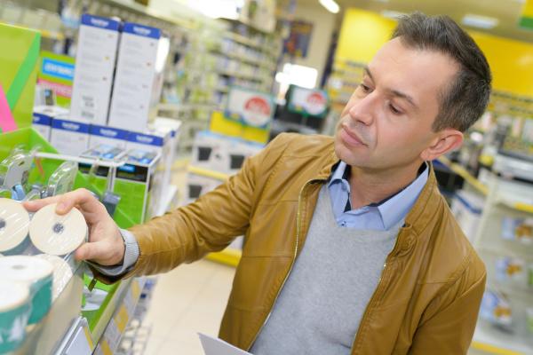 handsome man shopping in supermarket pushing