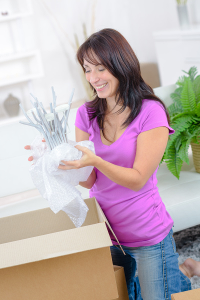 smiling woman with many cardboard boxes