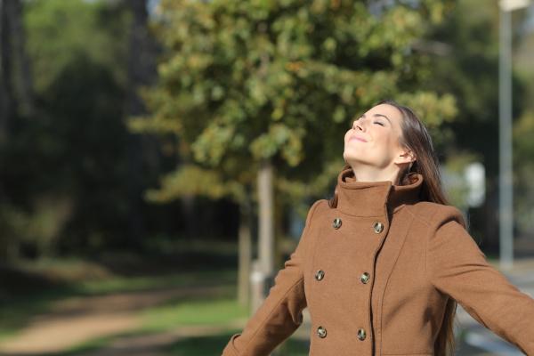 satisfied woman breathing fresh air in