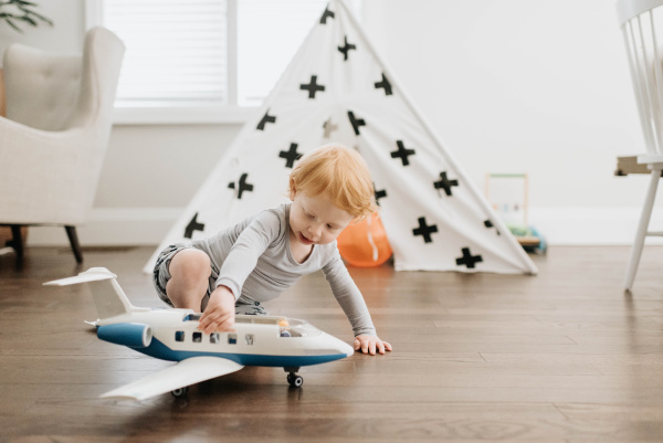 toddler playing with toy aeroplane in