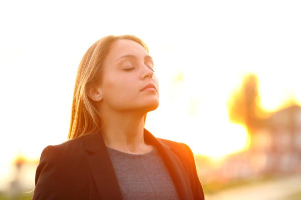 businesswoman breathing fresh air at sunset
