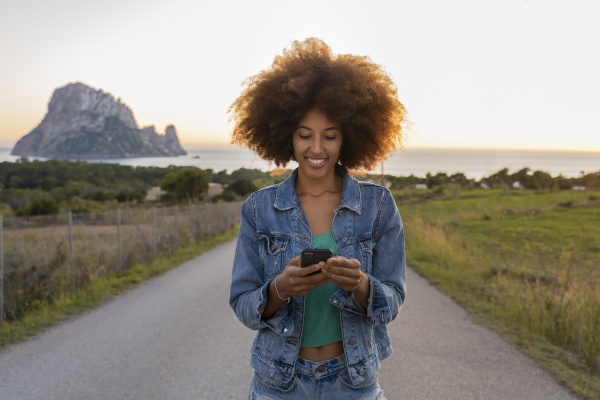 young woman on a road using