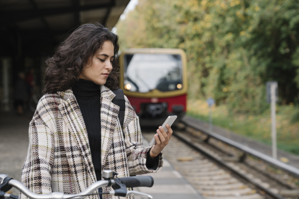 woman with bicycle and cell phone