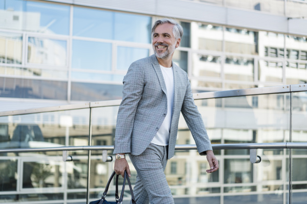 smiling fashionable mature businessman with bag