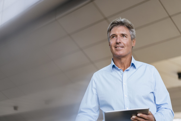 confident mature businessman with tablet in