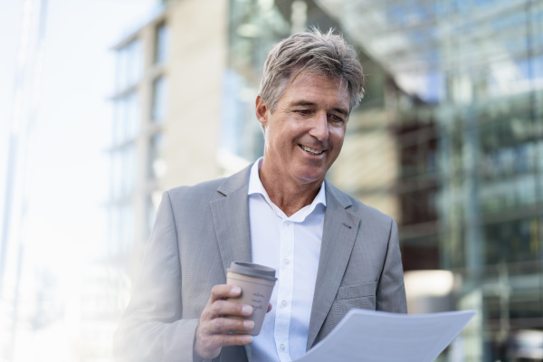 smiling mature businessman with takeaway coffee