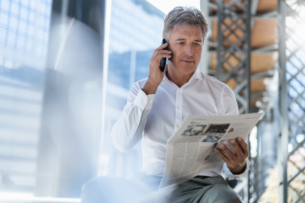 mature businessman with newspaper on the