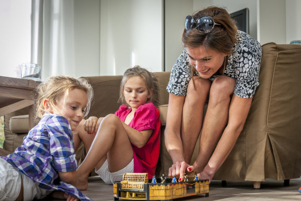 mother playing with daughters in living