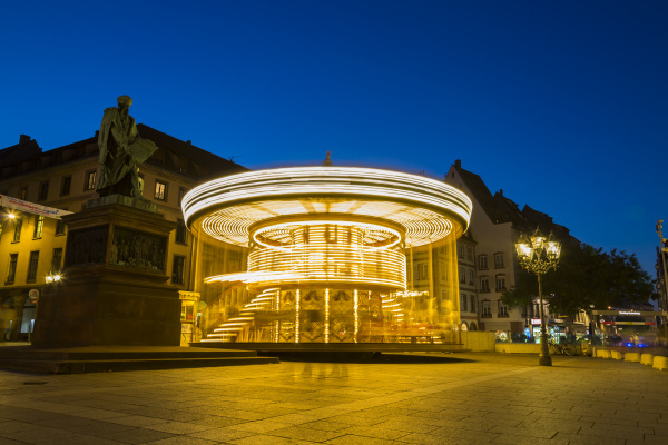 blurred motion of illuminated carousel against