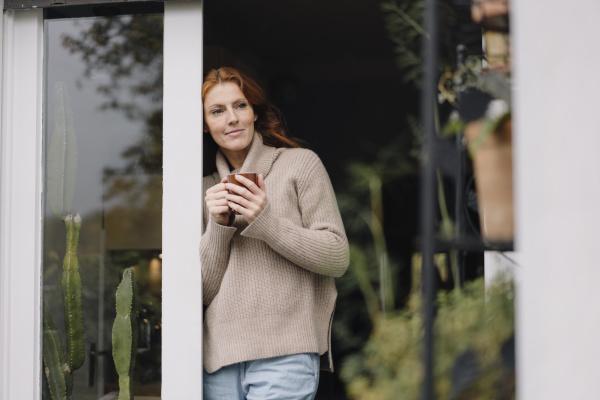 woman leaning in door drinking coffee