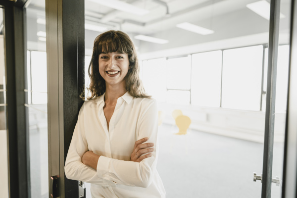 smiling businesswoman standing in an open