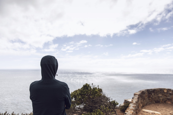 back view of man wearing hooded
