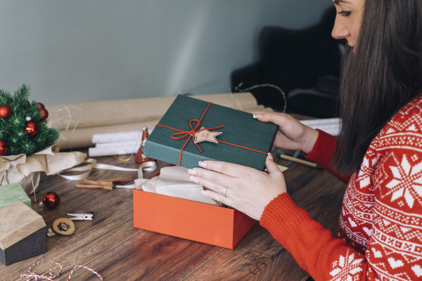 womans hands decorating christmas present