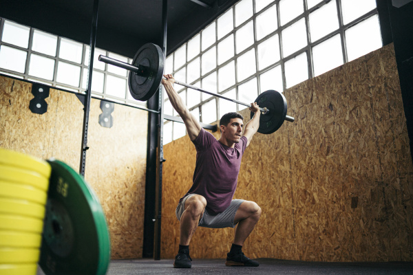 young man doing overhead squat exercise