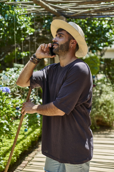 man with broom using his smartphone