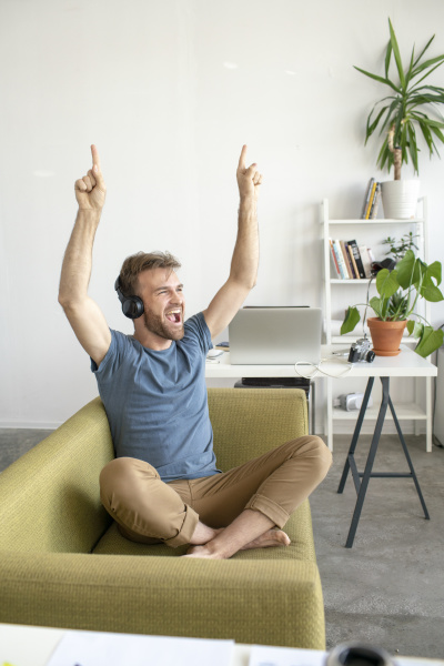 excited man sitting on couch in