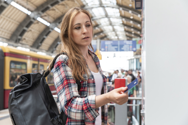 woman at train station buying train