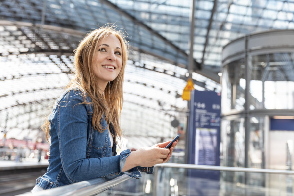 smiling woman with smartphone at