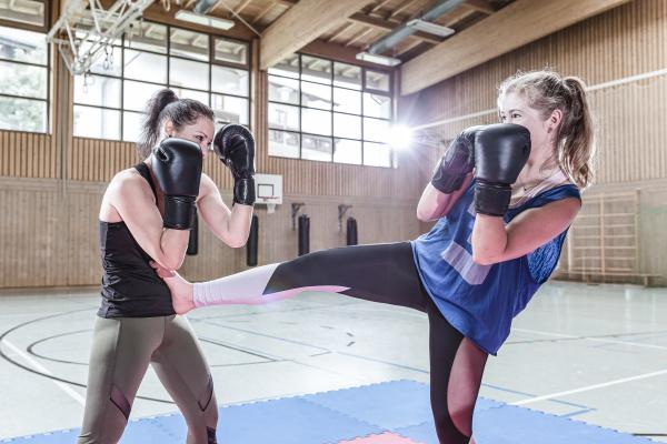 female kickboxers practising in sports hall