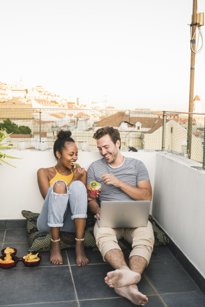 happy young couple with laptop sitting
