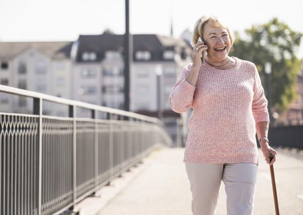 senior woman walking on footbridge using