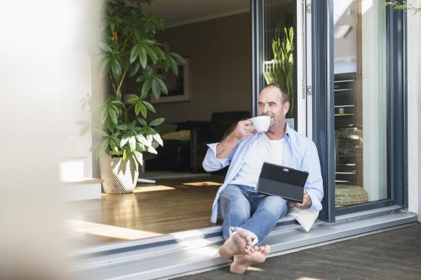 mature man sitting at terrace door