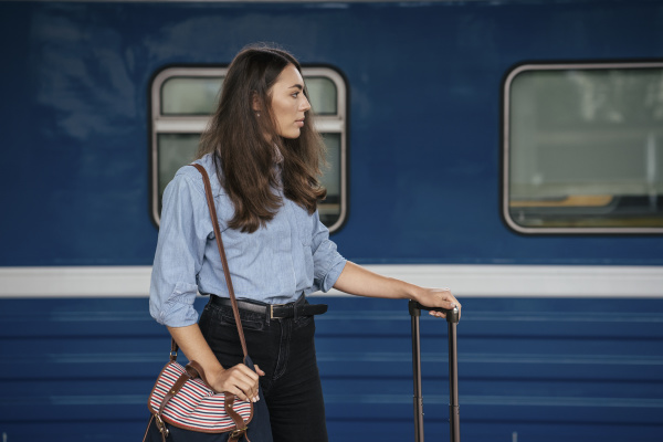 young female traveller waiting on traing