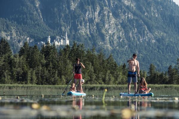 family paddle boarding on lake bannwaldsee