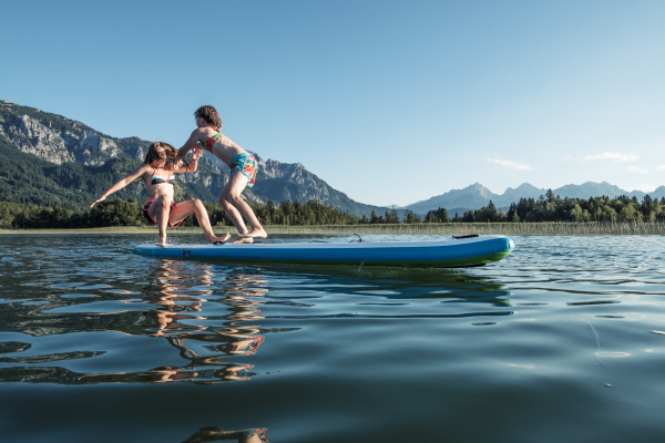 sisters fighting on paddle board