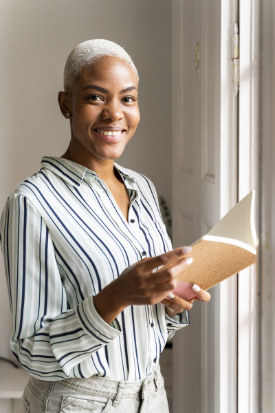 portrait of smiling woman with notebook