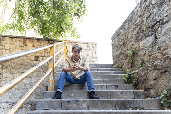 man sitting on outdoor stairs using