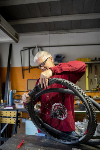 senior man repairing bicycle tire in