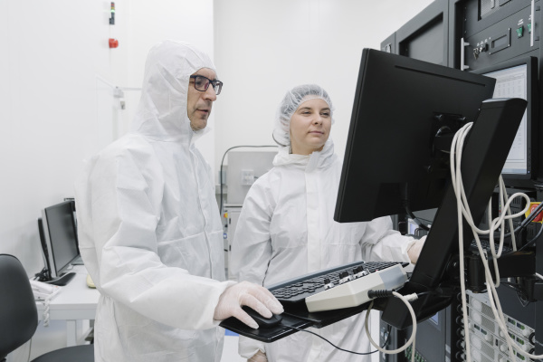 two scientists using computer in laboratory