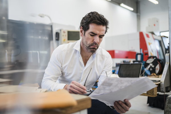 businessman reading paper in a factory