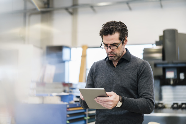 businessman using tablet in a factory