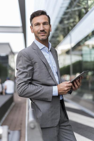 portrait of confident businessman with tablet