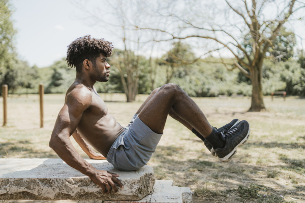 young man lifting legs during workout