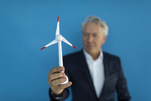 senior businessman holding wind turbine model